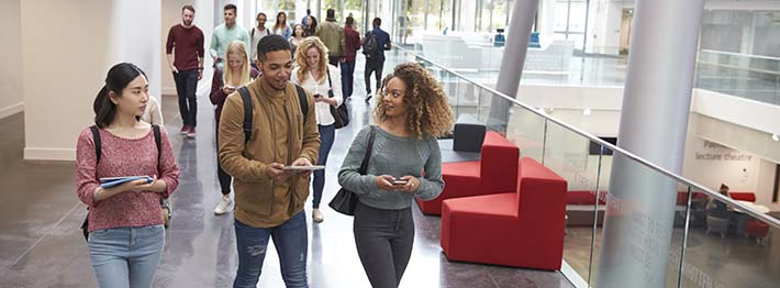 Students walk and talk using mobile devices in a college