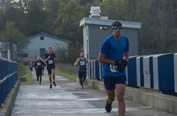 International student Andy Kamra running over a bridge during a 5km race