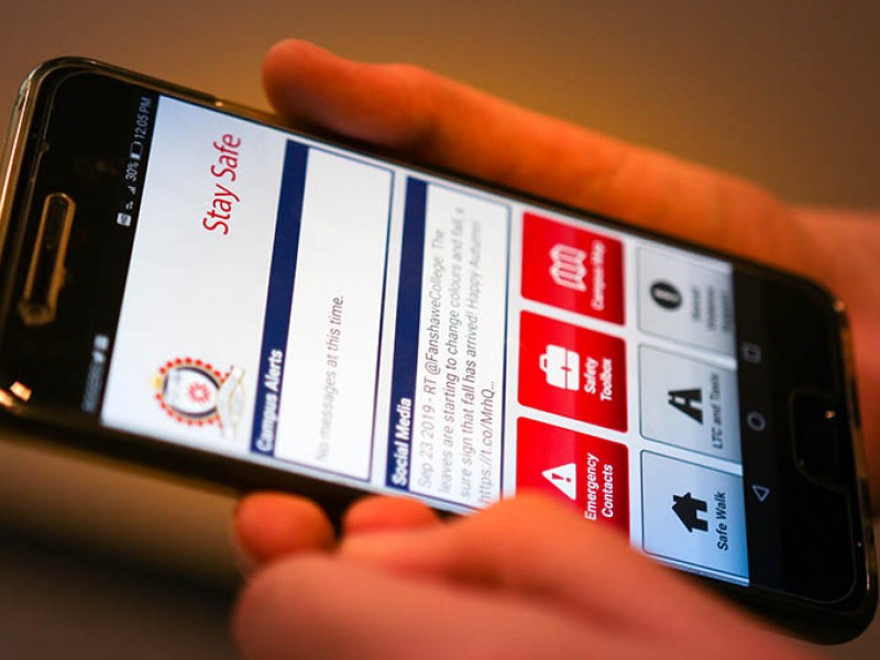 Fanshawe College student holding phone which displays a security alert