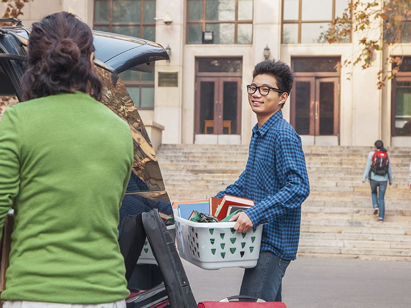 A new student carriers his belonging into residence.