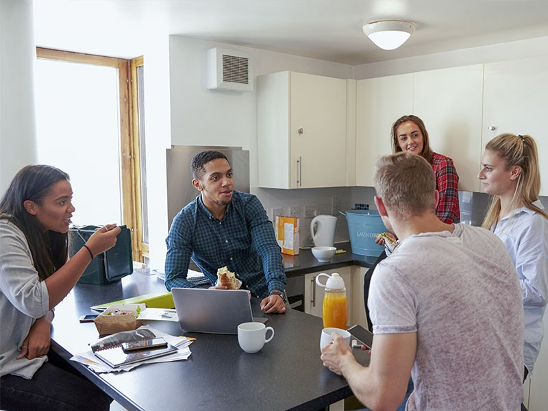 Students gather in the kitchen of an off-campus house
