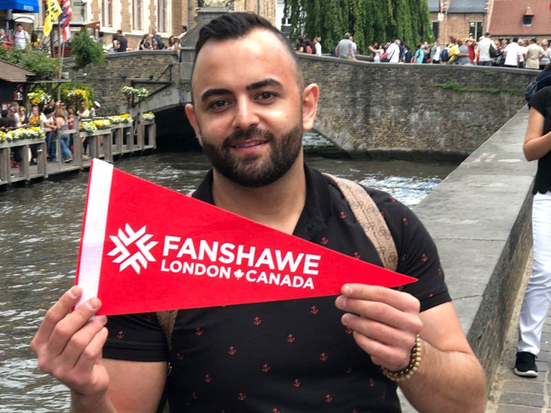 Omar Hachem holds Fanshawe Banner in Belgium