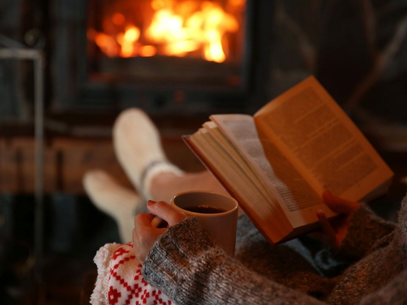 Reading a book near a fireplace