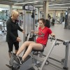 Student uses weight machine under guidance of Student Wellness Centre personal trainer
