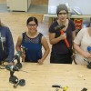 Female students working in carpentry shop with woodworking equipment
