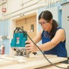 Female student working in carpentry shop with woodworking equipment