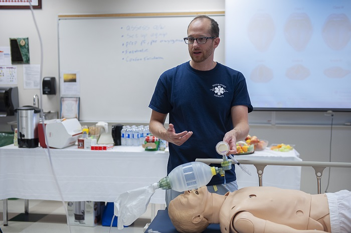 Professor gives instruction to students on intubating a patient