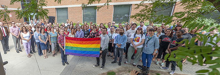 Students and staff holding up rainbow pride flag at London Campus